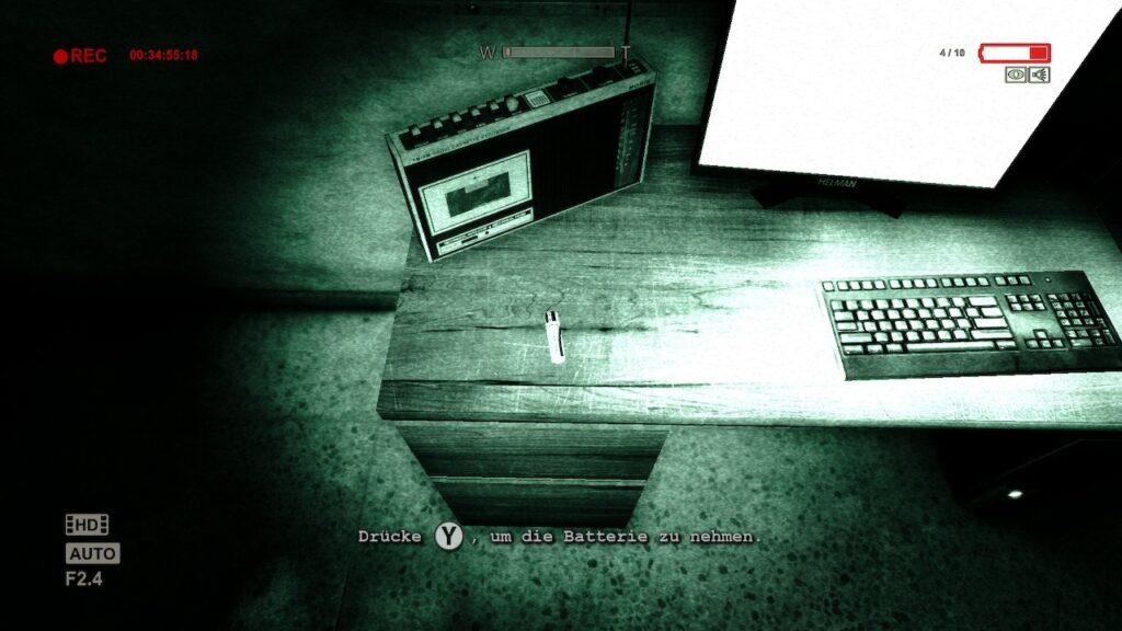 Aufleuchtende Batterie für Camcorder liegt auf einem Schreibtisch.
