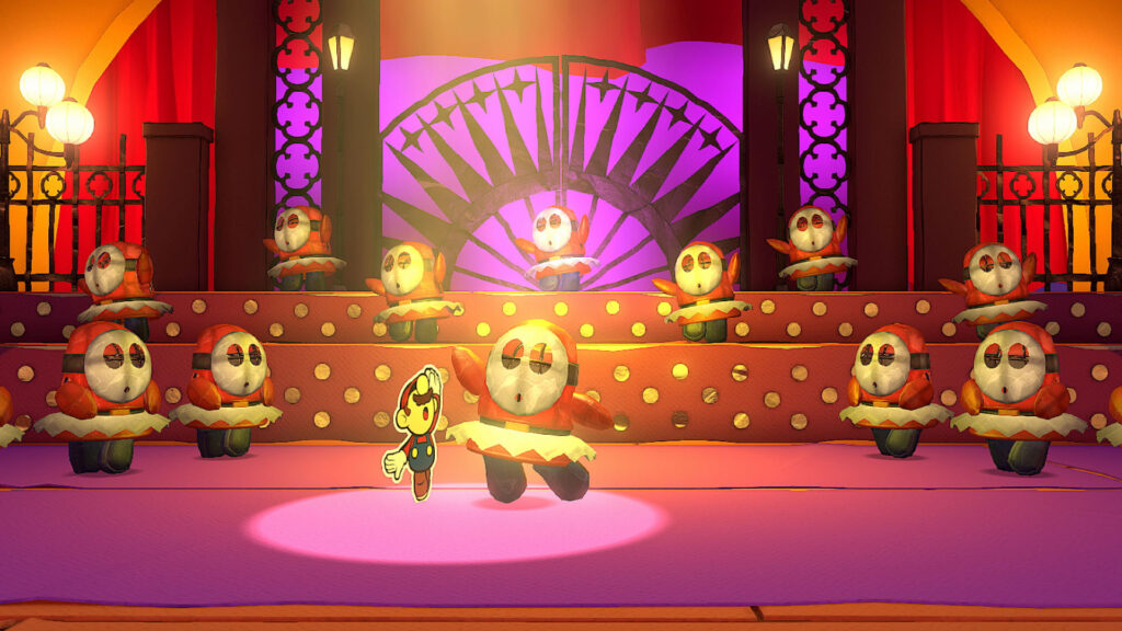 """Das Bild zeigt, wie Paper Mario mit einem Shy Guy in """"Paper Mario: The Origami King"""" Ballet tanzt."""