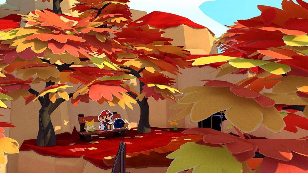 """Das Bild zeigt Paper Mario, Olivia und Bob-omb im Autumn Mountain. Es handelt sich um eine Szene aus dem Spiel """"Paper Mario: The Origami King""""."""
